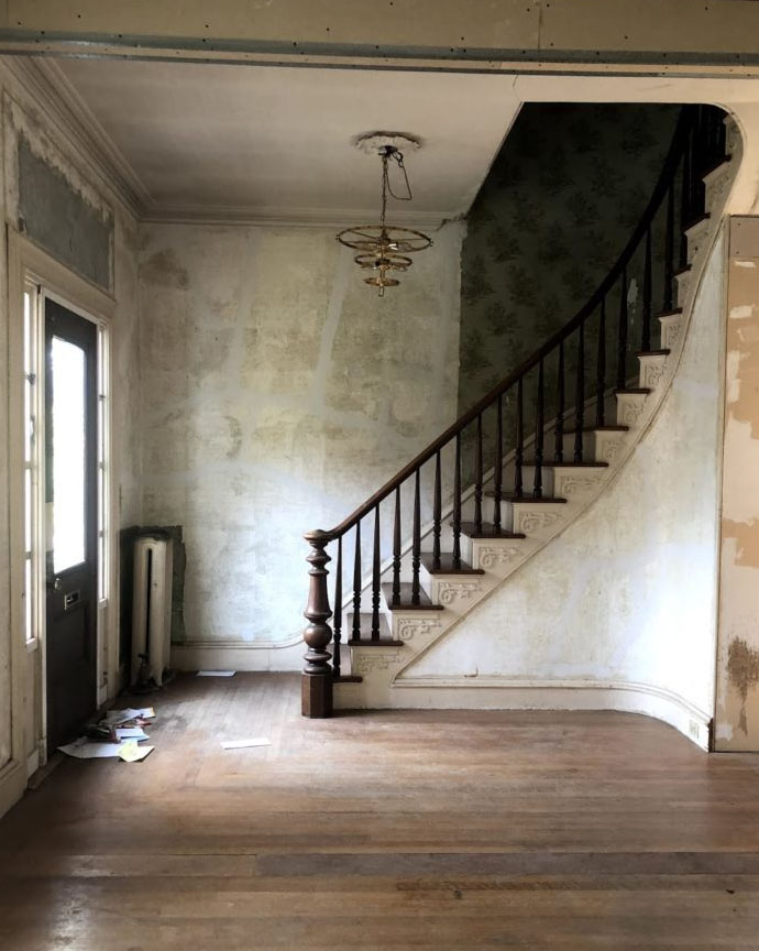 historic home descending staircase entryway with unfinished walls