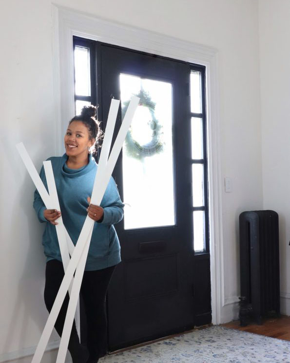 woman holding PVC trim posing by her front door