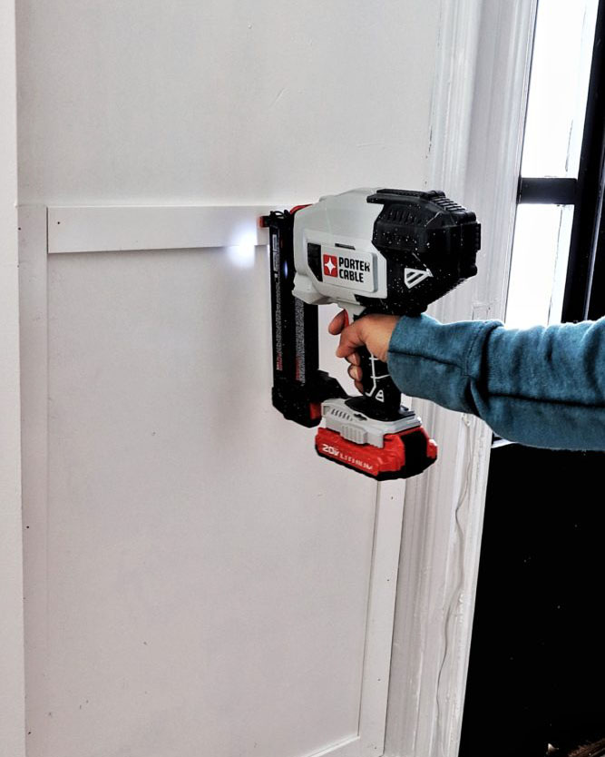 woman nailing PVC trim strips to wall with a nail gun