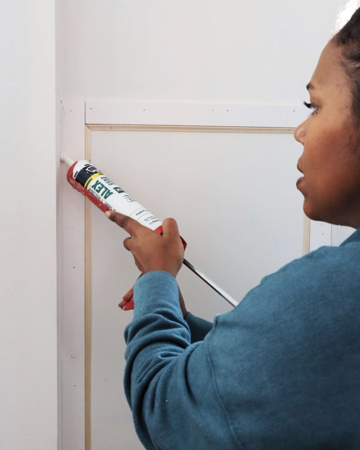 woman using spackle gun to fill gaps in trim application on wall