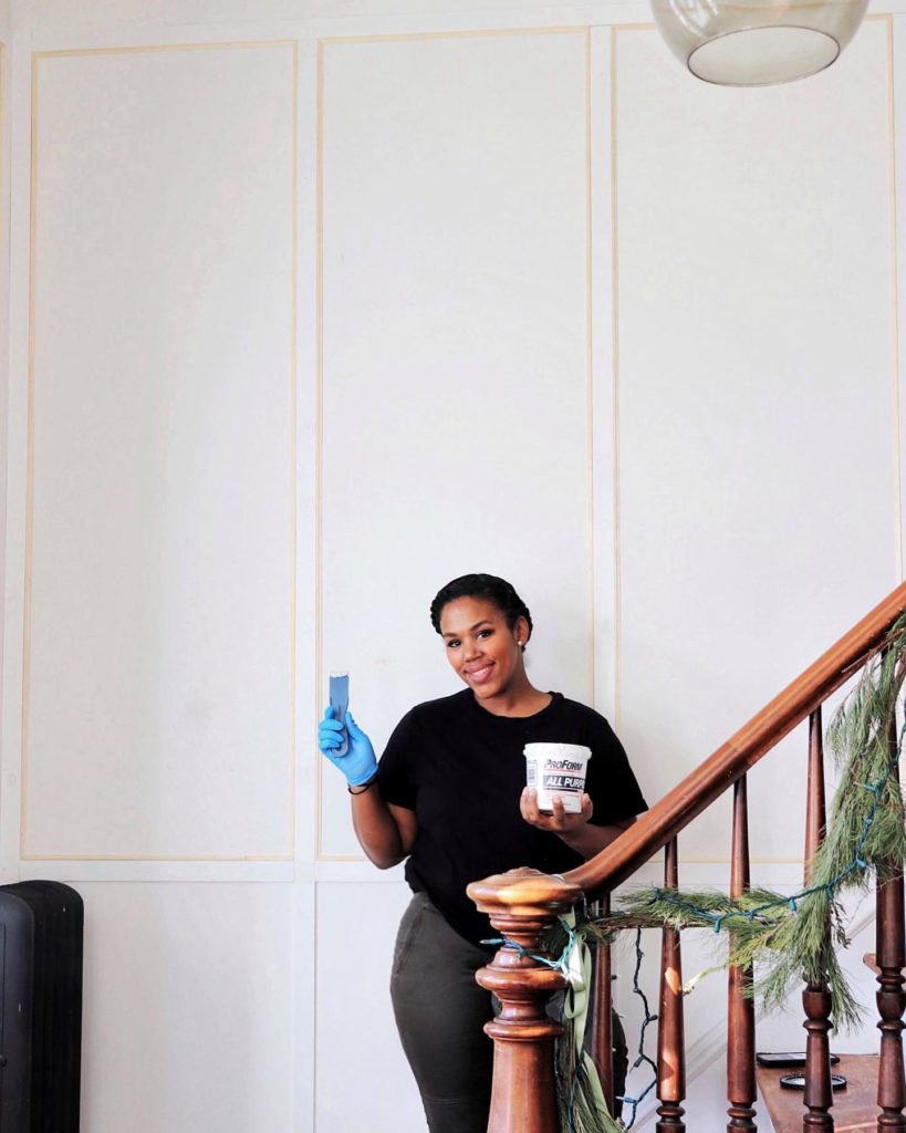 woman happily posing with spackle by her bare wall wearing gloves