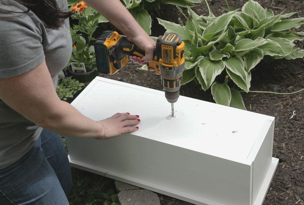 woman drilling a hole into the bottom of a white box