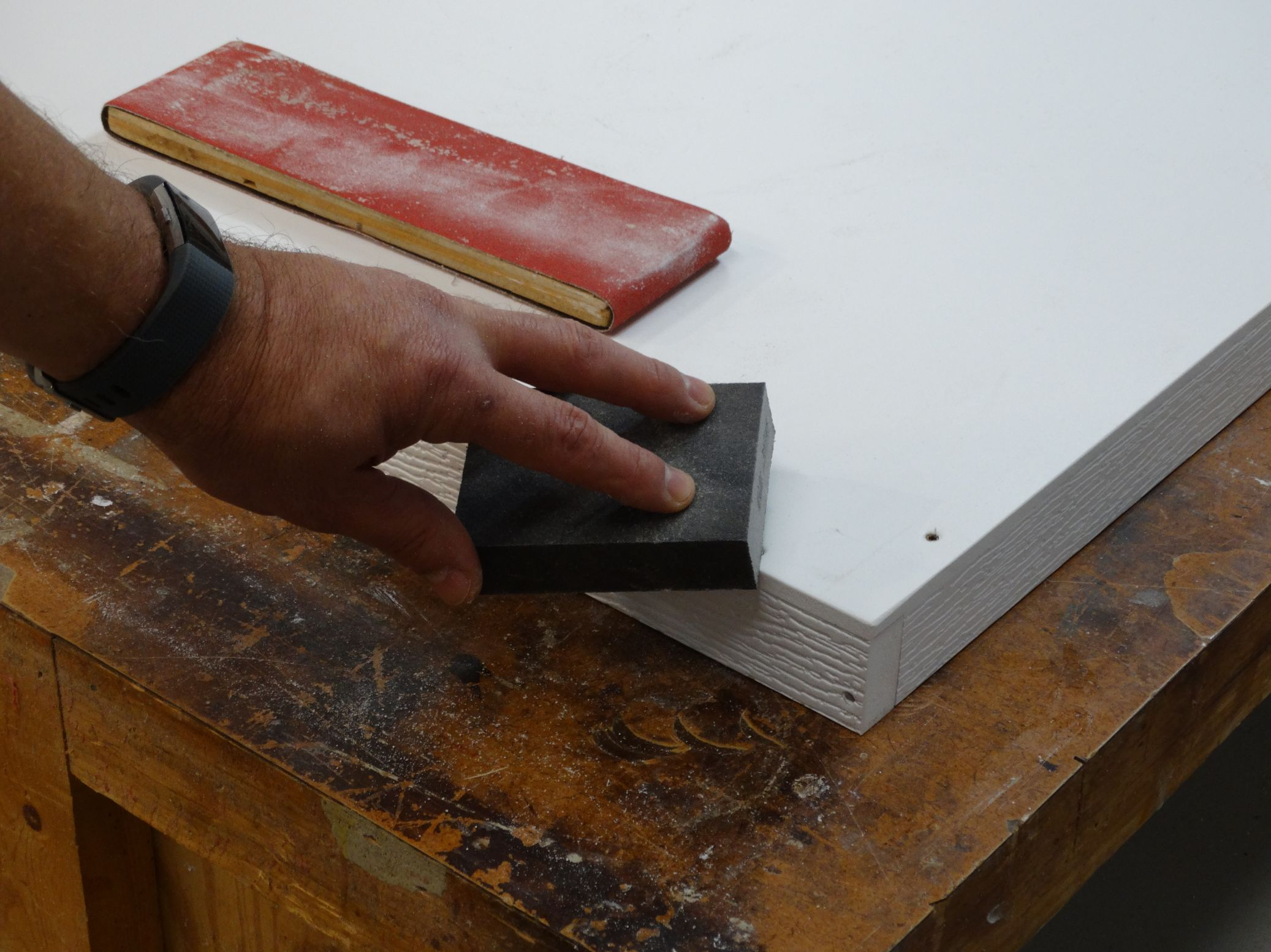 man sanding edges of white wood cut